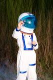 宇航员诉讼飞行玩具飞机的新男孩 免版税库存图片