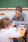 女小学生文字的画象与她的老师的 免版税图库摄影