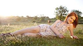 绿草域的女孩在日落。 免版税库存图片