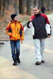 走在公园的父亲和儿子 免版税库存照片
