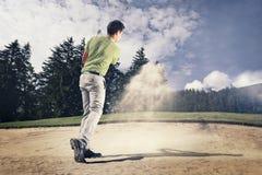 砂槽的高尔夫球运动员。 库存图片