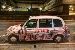 伦敦与给油漆工作做广告的出租车 免版税库存图片
