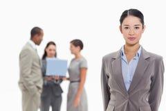有工友的严肃的女实业家在背景中 免版税库存图片