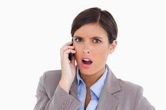 她的移动电话的恼怒的女性企业家 库存照片