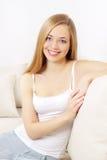 女孩坐的微笑的沙发 图库摄影