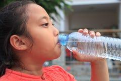 喝从瓶的女孩淡水 免版税库存照片
