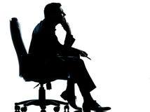 坐在扶手椅子剪影的一个商人 免版税库存图片