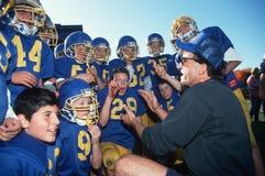 与青年橄榄球队的教练 图库摄影
