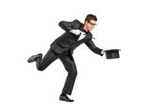 暂挂一魔术鞭子和打手势的魔术师 免版税库存照片