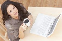 用膝上型计算机饮用的茶咖啡的妇女 免版税库存图片