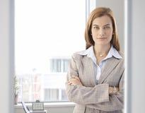 微笑在明亮的办公室的确信的女实业家 免版税库存图片