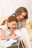 Внучка помощи бабушки делая домашнюю работу Стоковые Фото