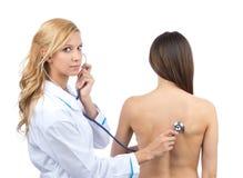 听诊的医生耐心的妇女年轻人 免版税库存图片