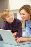 使用膝上型计算机的母亲和儿子在国内厨房 免版税库存照片