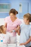 清洗牙的母亲和子项在卫生间里 免版税库存照片