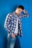 голубые джинсыы джинсовой ткани укомплектовывают личным составом детенышей рубашки шотландки Стоковые Фото