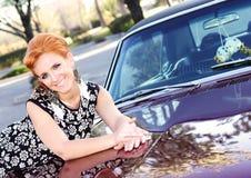 有肌肉汽车的俏丽的妇女 库存图片