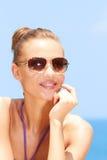 海滩的俏丽的妇女与太阳镜 免版税库存图片