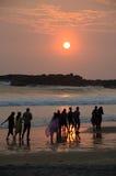 海滩人漫步日落采取 免版税库存图片
