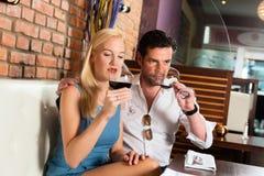 喝红葡萄酒的有吸引力的棒夫妇 免版税图库摄影