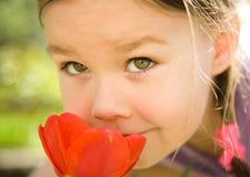 χαριτωμένο κορίτσι λουλουδιών λίγη μυρωδιά πορτρέτου Στοκ Φωτογραφίες