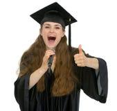 兴奋毕业话筒告诉的学员 免版税库存图片