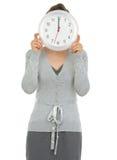 企业时钟表盘前显示的妇女 免版税库存图片