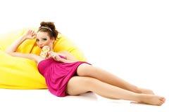 Γυναικών η όμορφη καραμέλα γλειψιμάτων σύνθεσης νέα στον κίτρινο καναπέ απομονώνει Στοκ Φωτογραφίες