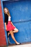 相当十几岁的女孩红色裙子蓝色门 库存照片