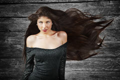 Женщина брюнет с длинними волосами над деревянной предпосылкой Стоковое Изображение