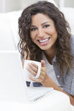使用膝上型计算机的妇女饮用的茶咖啡 免版税库存照片