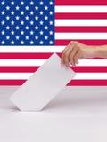 投入一张投票的选票的夫人手在美国的白色箱子槽孔  免版税图库摄影