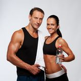 有瓶的微笑的运动的男人和妇女 库存图片
