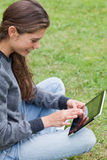 成人交叉有腿的坐的微笑的年轻人 库存照片
