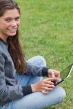 坐下与她的片剂个人计算机的微笑的女孩 图库摄影