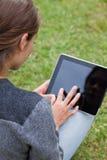 使用她的片剂个人计算机的一个女孩的背面图 免版税库存照片