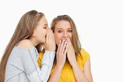 白肤金发的学生耳语对她无声的朋友 免版税库存照片