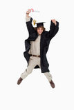 毕业生跳的男性长袍学员 免版税库存图片