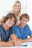 三位微笑的学员,他们查看照相机 免版税库存图片