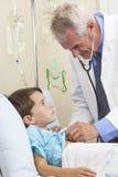 男孩儿童医生检查的男性耐心的年轻人 免版税库存图片