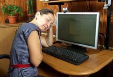 休眠在计算机附近的妇女 免版税库存照片