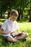 有片剂个人计算机的男孩 免版税库存图片
