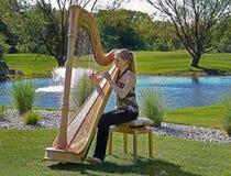 弹在高尔夫球场的妇女一把竖琴 免版税图库摄影