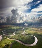 Δασικός ποταμός κάτω από τα άσπρα σύννεφα Στοκ Φωτογραφία