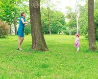 演奏捉迷藏的母亲和女孩 免版税库存照片