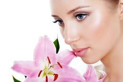 Όμορφο κορίτσι με έναν κρίνο λουλουδιών Στοκ Εικόνες