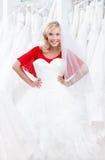 试穿一件引人入胜的婚礼服 免版税图库摄影