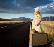 在路的端的女孩带着手提箱的 免版税库存照片
