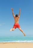 跳在海滩的人 免版税库存照片