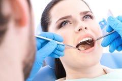 牙科医生检查患者的牙 免版税图库摄影